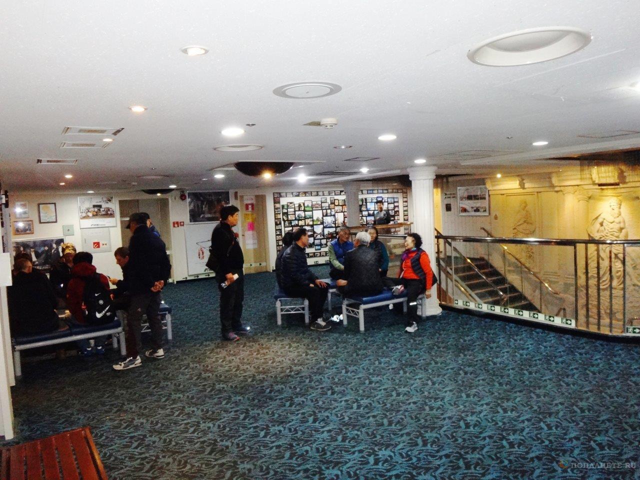 Пассажиры дешевых кают часто проводят время в холле парома